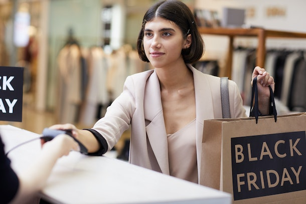 Portrait of elegant young woman buying clothes standing at cashier desk while shopping in mall in sale season, copy space