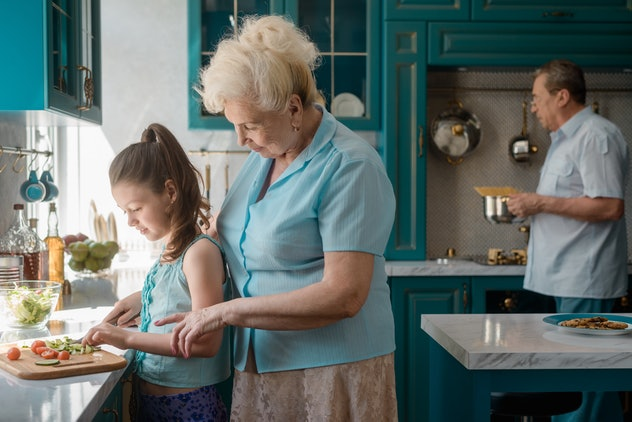 Girl and grandmother cutting vegetables, while grandfather cooking pasta. Leaving a kid with grandparents.