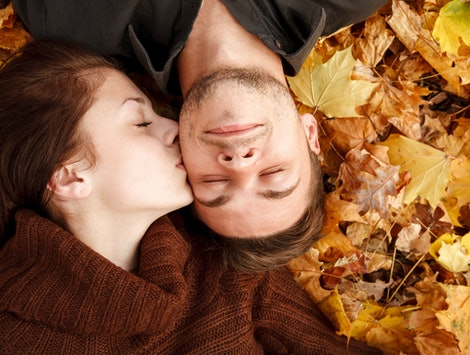 young couple lying down on autumn leaves eyes closed she kissing him