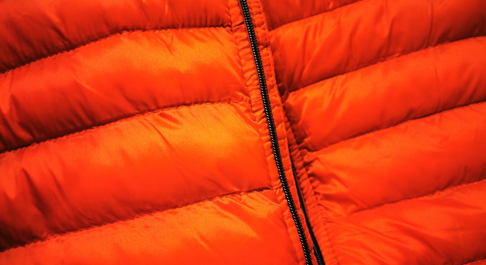 puffer jacket closeup in vivid bright red fabric material with black zip