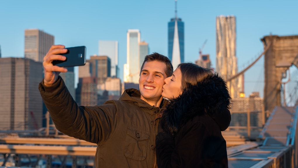 A couple poses for a selfie with NYC skyline in the background.