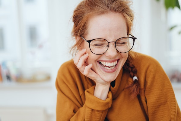 Pretty red-haired girl with pigtail, wearing glasses and orange sweatshirt, laughing with her eyes closed. Close-up front portrait indoors with copy space