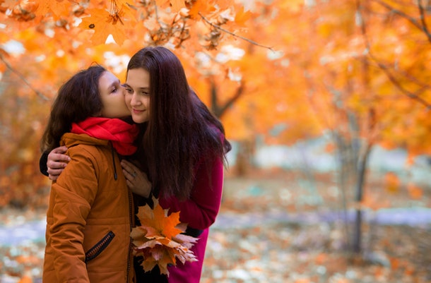 Beautiful teenager daughter kisses mother on the cheek for a walk in the park in fall. A kid in a scarf and an orange jacket, a woman in a red coat, holding a bouquet of maple leaves. Horizontal photo