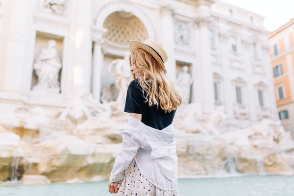 A stylish woman poses in front of the Trevi Fountain while studying abroad in Rome.