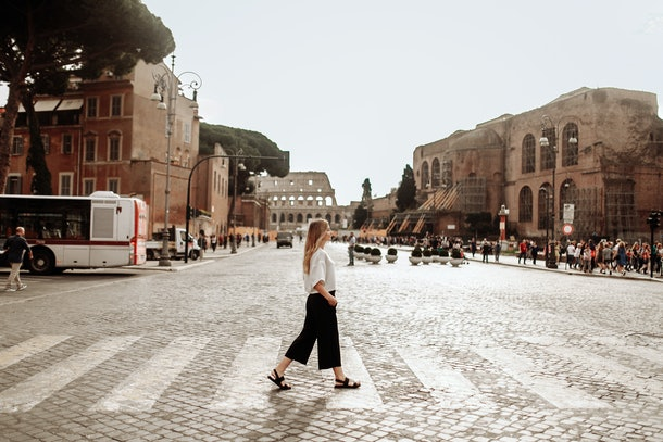 A blonde woman walks on a crosswalk near the Colosseum in Rome while studying abroad.
