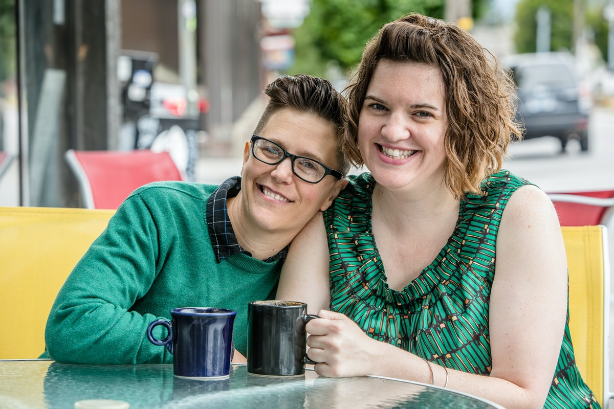 Woman leaning on shoulder of female spouse at outdoor coffee house