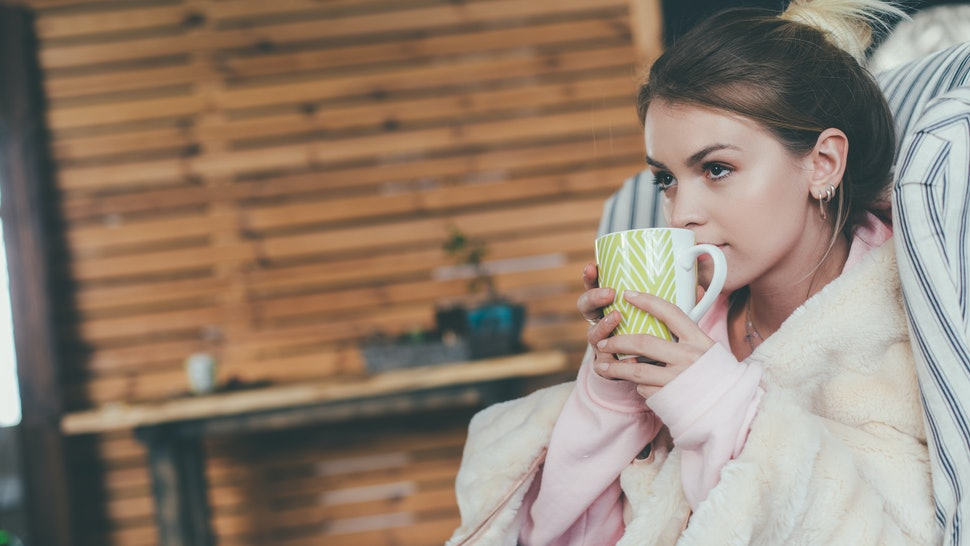 Young beautiful attractive woman in cozy clothes sitting alone in chair. Hold cup with hot drink and touch it with lips. Thoughtful calm and peaceful. Attentive. One in room