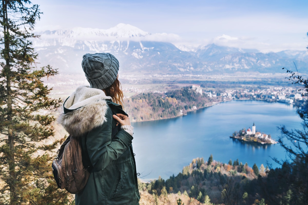 Hiking young woman with alps mountains and alpine lake on background. Travel Slovenia, Europe. Top v...