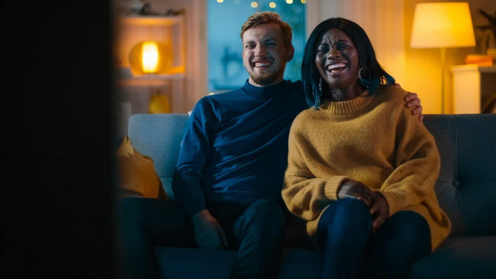 Happy Diverse Young Couple Watching Comedy on TV while Sitting on a Couch, they Laugh and Enjoy Show. Handsome Caucasian Boy and Black Girl in Love Spending Time Together in the Cozy Apartment.