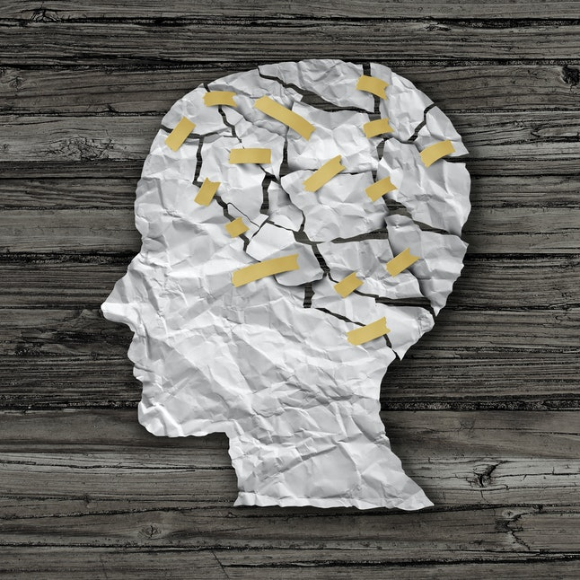 Brain disease therapy and mental health treatment concept as a sheet of torn crumpled white paper ta...