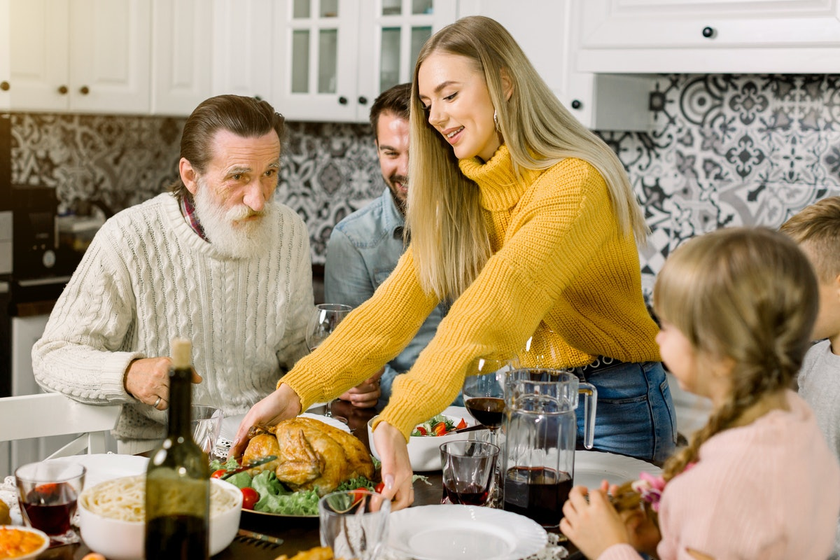 A blonde woman smiles and places the Thanksgiving turkey in the middle of the table for dinner, surrounded by her family members.