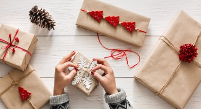 Creative hobby. Woman's hands wrap christmas holiday handmade present in craft paper with twine ribb...