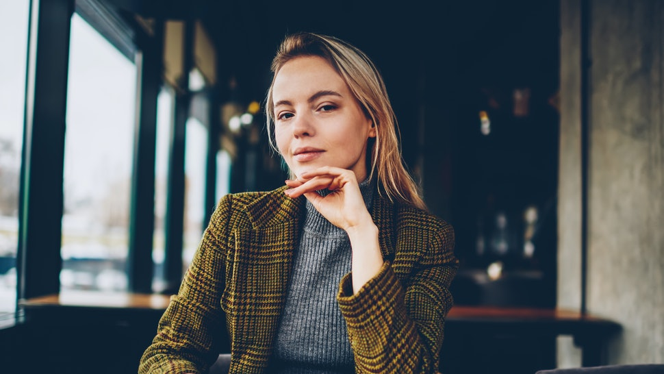 Half length portrait of confident businesswoman dressed in stylish jacket looking at camera.Serious female entrepreneur with smartphone in hand sitting at wooden table in cafe interior