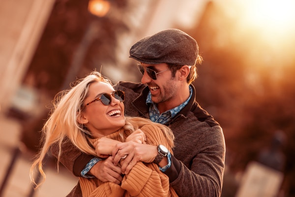 A couple in fall clothes and sunglasses hugs and laughs in the sunshine on Thanksgiving.