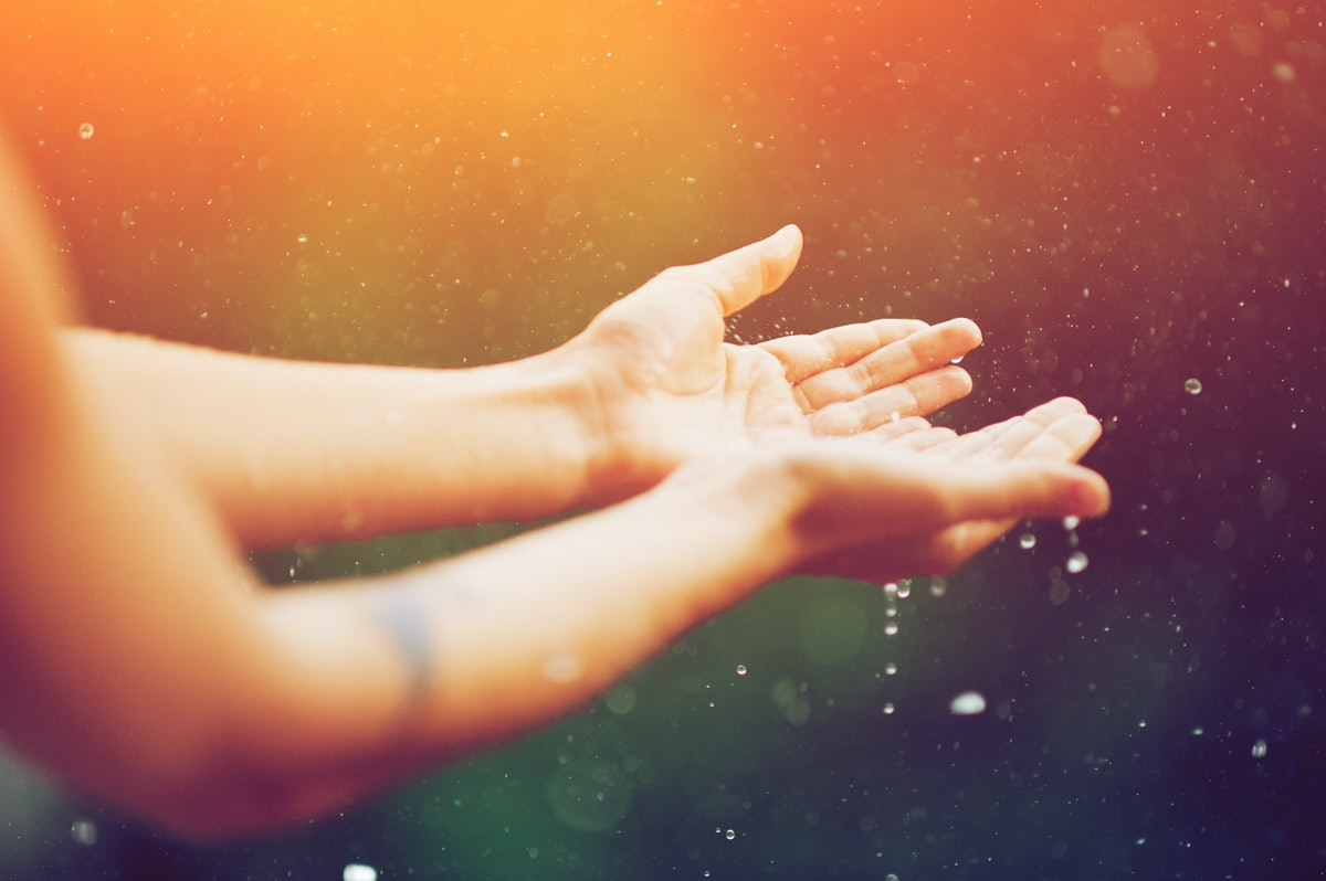 hand catching rain drops on blurred background. Woman hands praying for blessing from god on sunset. Empowerment, sacred forgiveness, positive arm energy, good morning, reborn change concept.