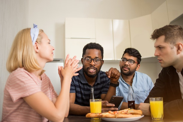 Group of diverse friends sitting at table, eating pizza, drinking juice, using mobile phone, friendly talking. Multicultural students having lunch in kitchen.