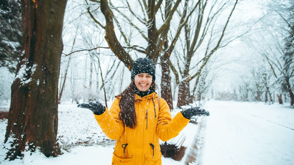 woman playing with snow in snowed city park