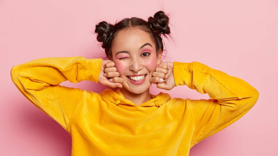 Image of lovely young Asian woman with happy face expression, blinks eye and smiles positively, has fun indoor, two hair knots, dressed in yellow velvet hoody, isolated over pink background.