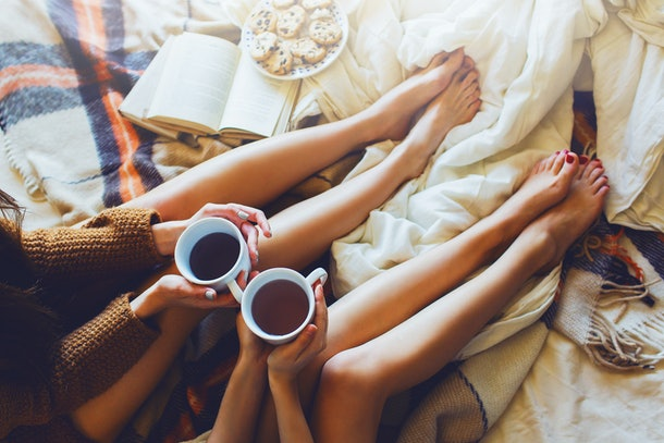 Two friends sit on a bed with cups of tea, blankets, and cookies in the fall.