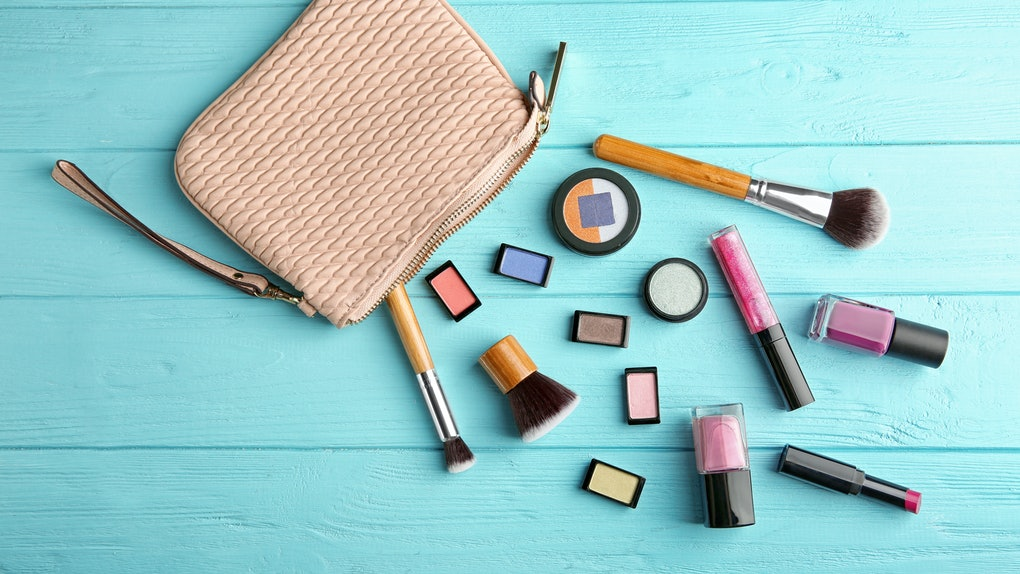 A beige-colored makeup bag on a blue table has cosmetic products and brushes next to it.