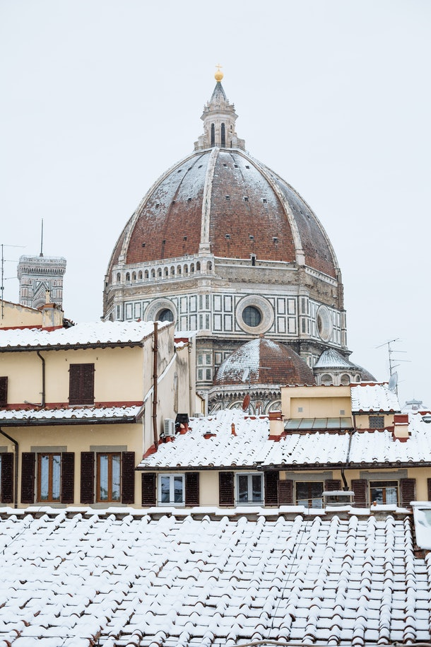 The Duomo in Florence, Italy is covered in snow around Christmastime.