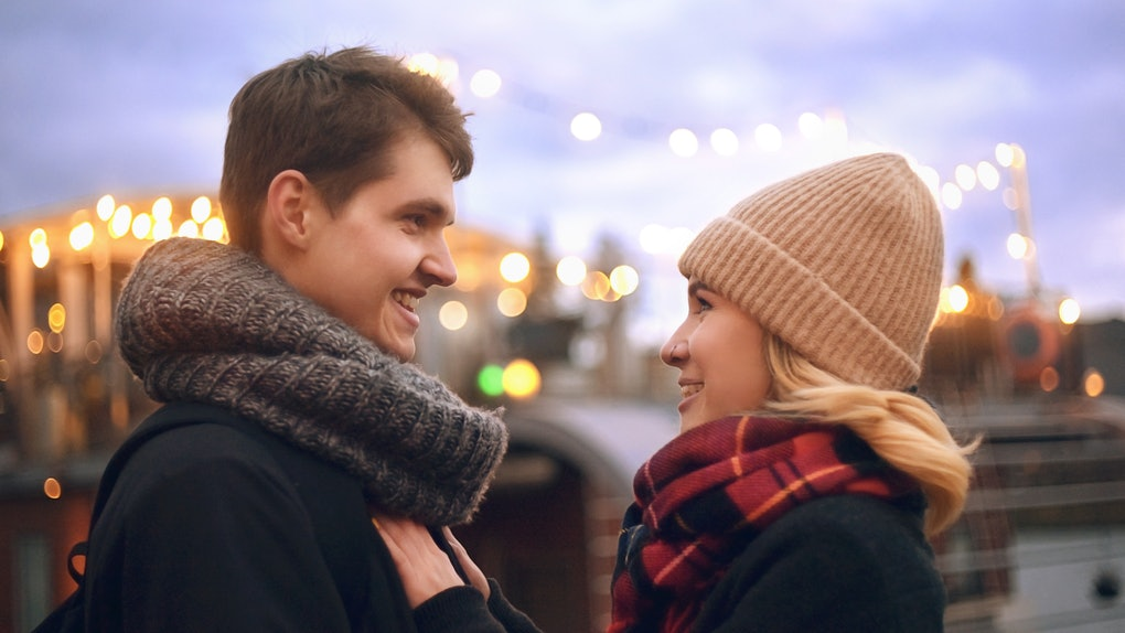 A young couple take a holiday photo together with Christmas lights in the background.