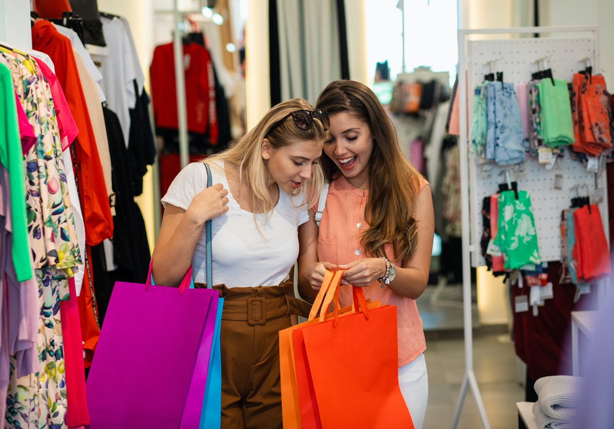 Two friends holding colorful shopping bags look at their findings in a store.
