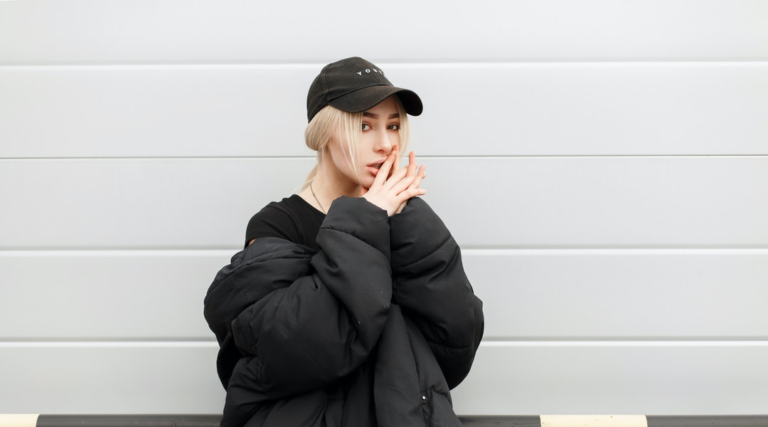 Fashion pretty model girl in fashionable black winter clothes with a cap near a modern metal wall