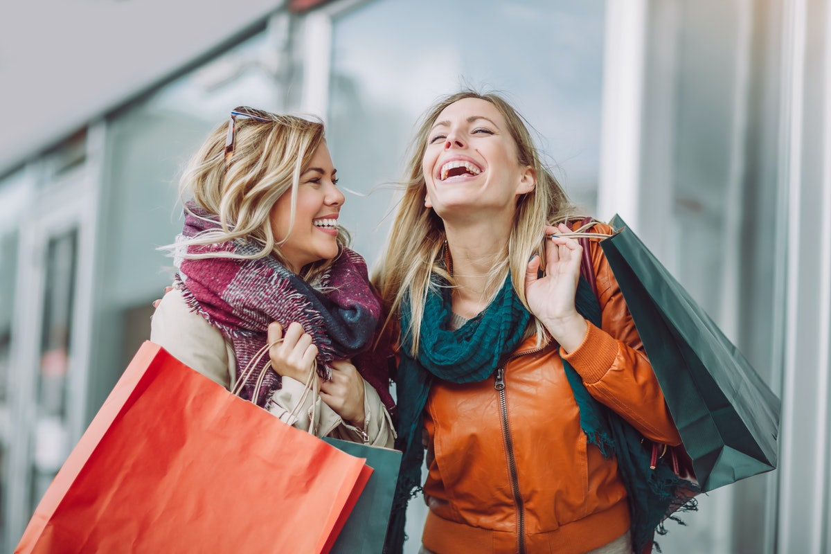 Two women laugh while they hold their shopping bags.