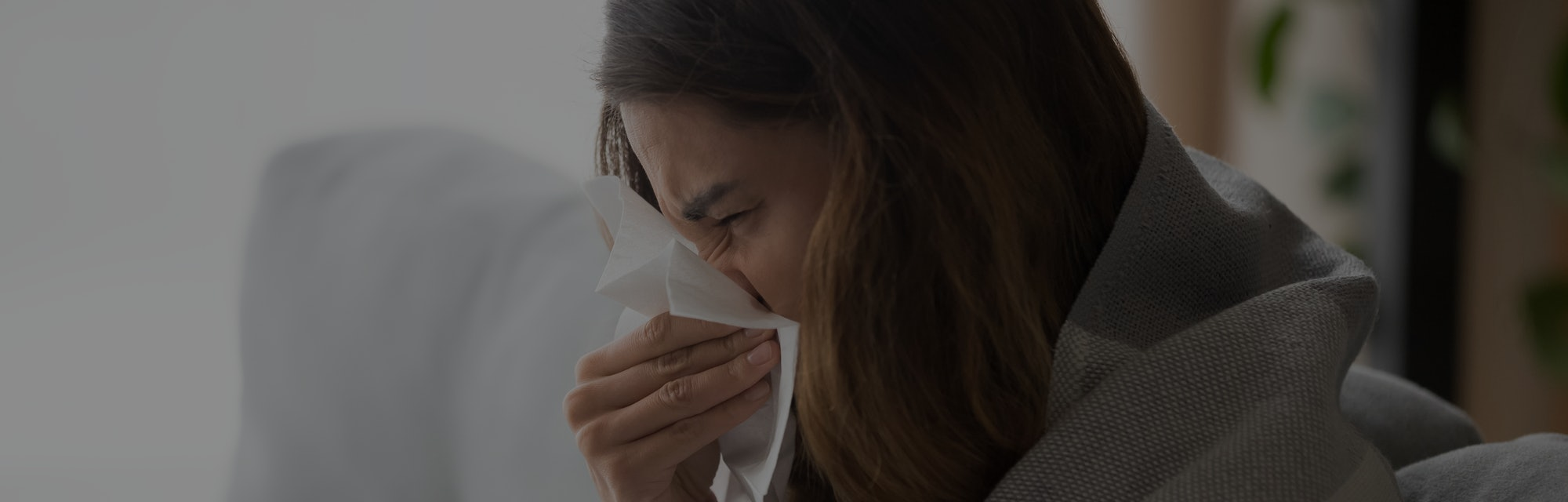 This woman blowing her nose could be staying home from work because of the flu.