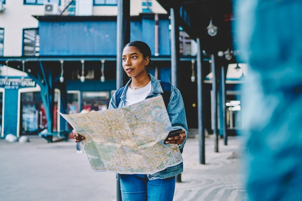 A woman holds a map and her phone outside of a train station in a major city.