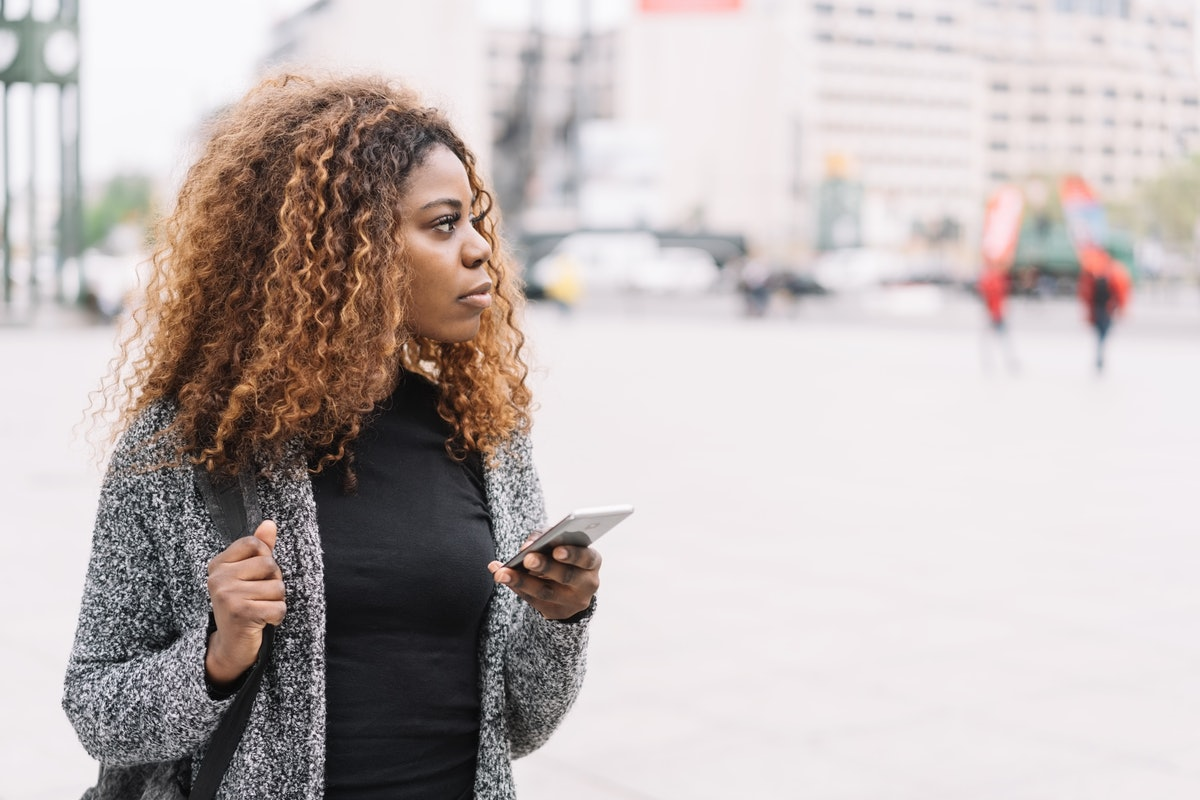 Woman holding phone, possibly cutting ties with someone she is in love with but can't be with.