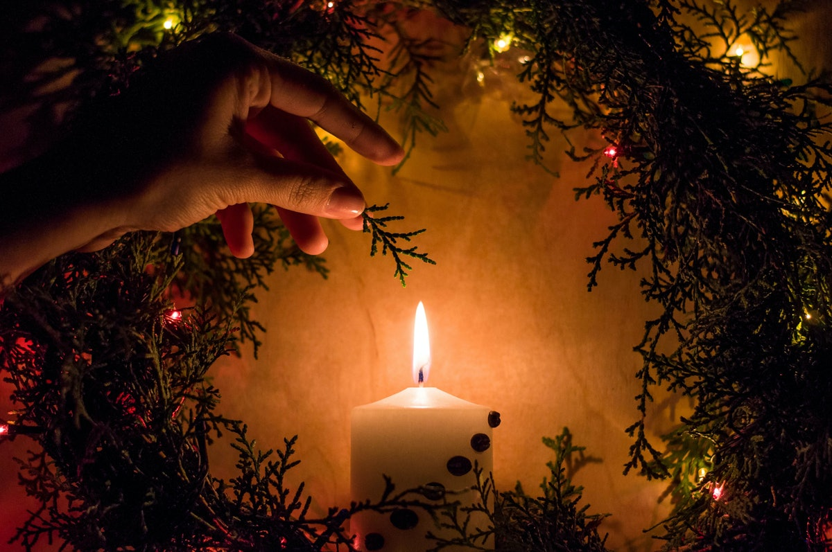Warm christmas candle with garlands in a wreath