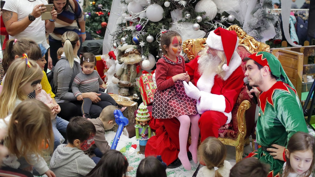 Children wait for their turn to the Santa gift moment while attending a Christmas Tree show dedicate...