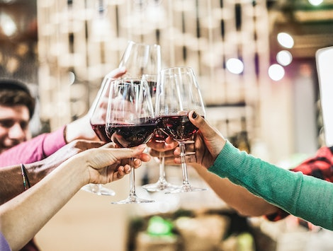 Group of diverse culture friends cheering with red wine in trendy winery bar - Happy people drinking and having fun pub restaurant after work - Party and nightlife concept - Focus on close up hands