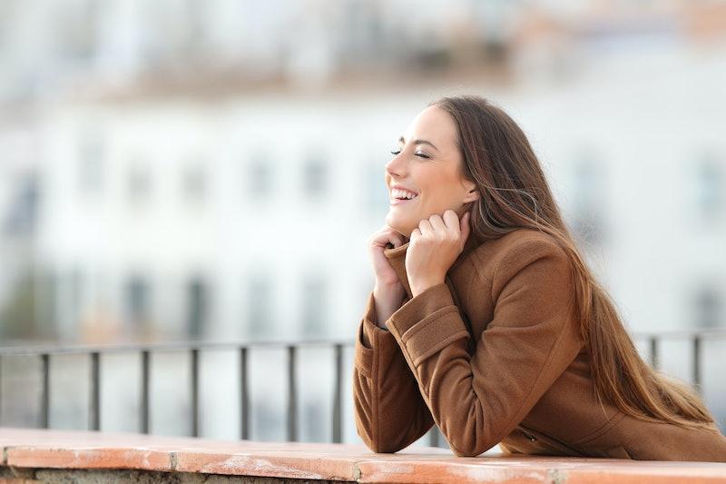 Happy woman heating grabbing jacket in a balcony in winter