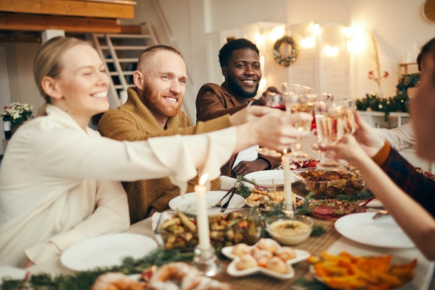 Multi-ethnic group of people raising glasses while celebrating Christmas with friends and family sit...