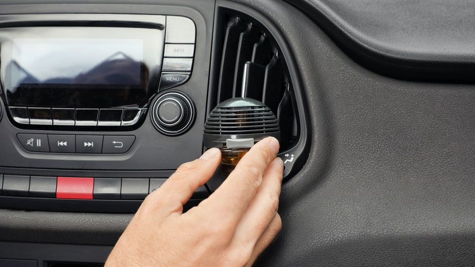 Man regulating air freshener near ventilation in car, closeup