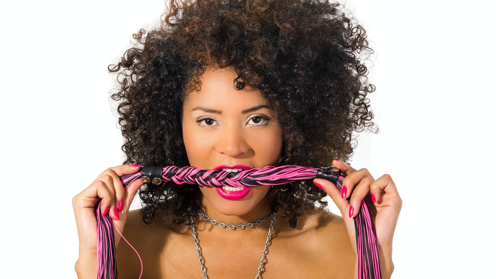 Close up shot of exotic beautiful young girl with dark curly hair posing holding whip isolated on white