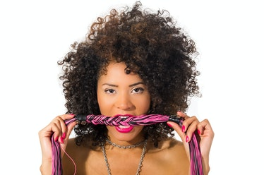 Close up shot of exotic beautiful young girl with dark curly hair posing holding whip isolated on wh...