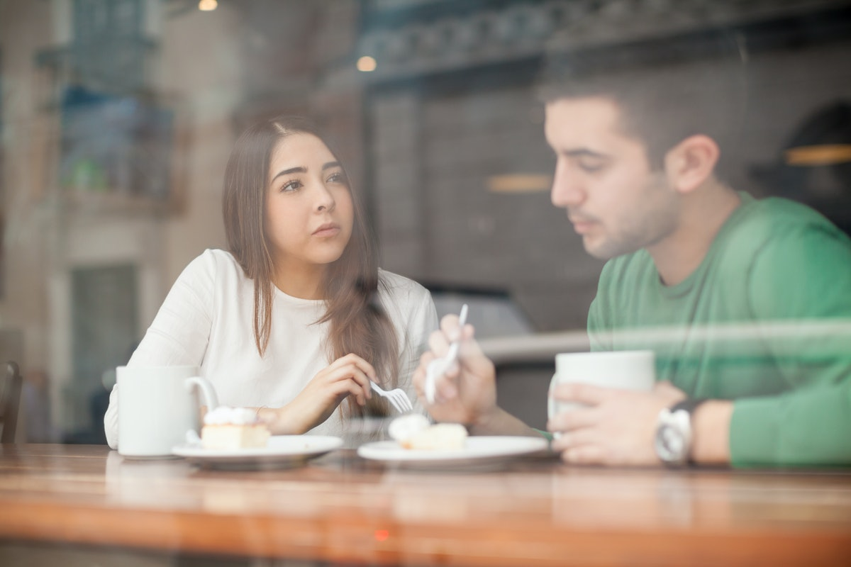Pretty young brunette talking to her boyfriend in a coffee shop and looking serious