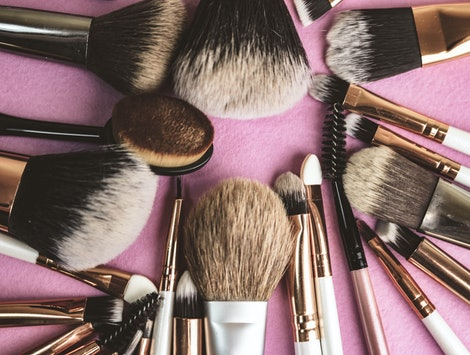 A set of beautiful different soft brushes for make-up from natural nap for beauty targeting and applying a tonal foundation in a stand and copy space on a pink, purple background.