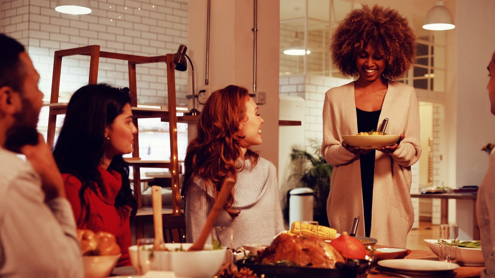 Front view of a young mixed race woman standing and holding a plate of food to serve her four young adult multi-ethnic male and female friends sitting around a table at home for Thanksgiving dinner