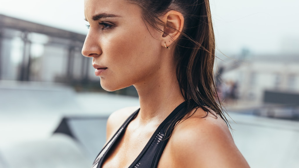Determined young woman in sportswear standing outdoors. Fit female athlete after workout in morning.