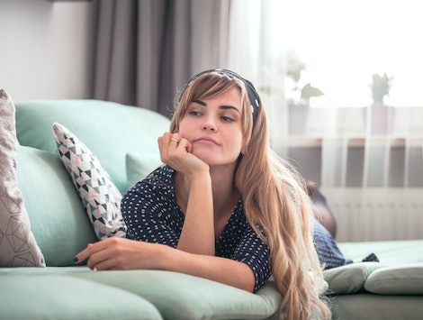 Sad disappointed woman lying on couch and thinking about something at home, casual style indoor shoot