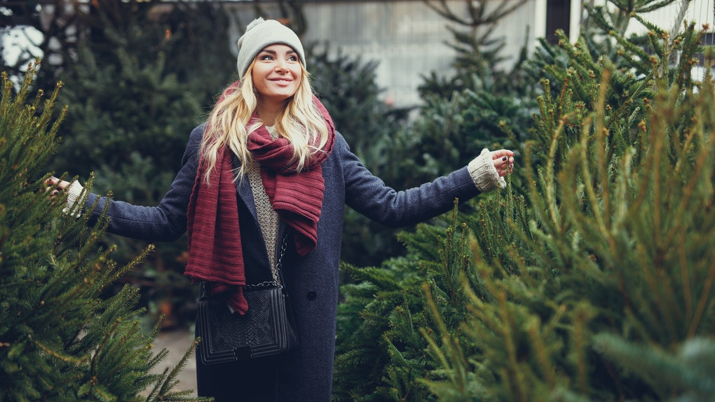 A blonde woman smiles and walks amongst a row of Christmas trees.