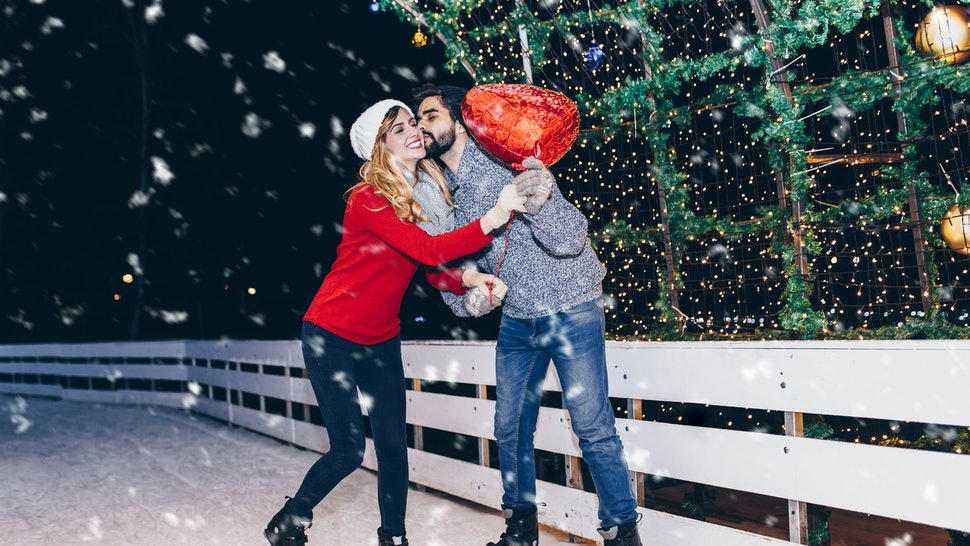 Happy romantic young couple enjoying together in ice skating.