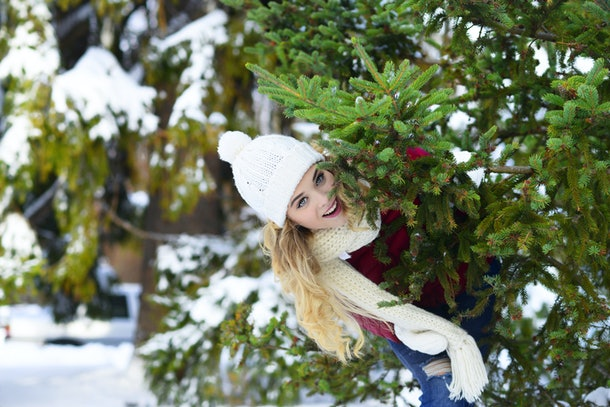 A blonde woman smiles and peaks out from behind a Christmas tree at a farm in the winter.
