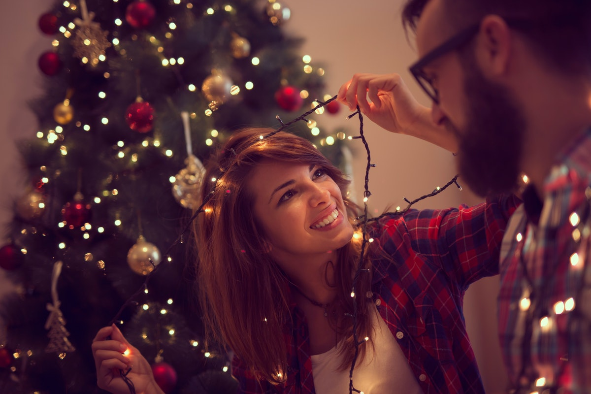 Beautiful young couple in love decorating Christmas tree, arranging the christmas lights and having fun