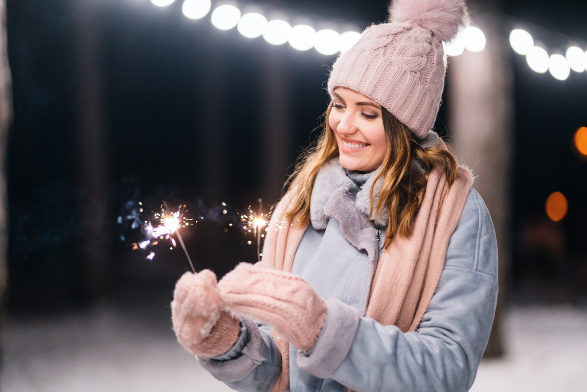 Beautiful girl with sparklers in hands. Happy winter time in the forest. The girl is dressed in a blue coat, in a light knitted hat, scarf and mittens. Festive garland lights. Christmas, new year.